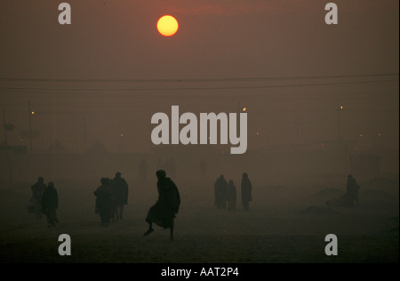 KUMBH MELA INDIA 2001 AS THE SUN SETS THE SMOKE FROM WOOD FIRES CREATES A THICK SMOG PILGRIMS RETURN TO THEIR CAMPS - Stock Photo