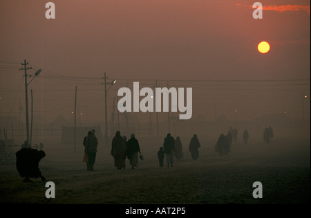 KUMBH MELA INDIA 2001 AS THE SUN SETS THE SMOKE FROM WOOD FIRES MAKES A THICK SMOG PILGRIMS RETURN TO THEIR CAMPS - Stock Photo