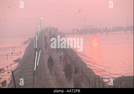 KUMBH MELA INDIA 2001 AS THE SUN SETS PILGRIMS MAKE THEIR WAY BACK ACROSS THE TEMPORARY BRIDGES TO THEIR CAMPS 2001 - Stock Photo