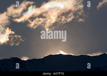 Light refracting in the clouds and high winds blowing snow of the mountain ridges above Val Venosta, South Tyrol, - Stock Photo