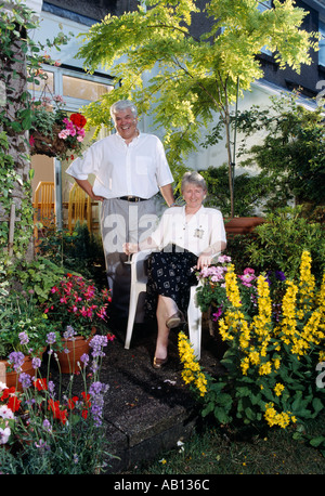 MIDDLE AGED COUPLE IN GARDEN WITH FLOWERS - Stock Photo