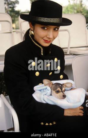 Rich Mexican woman with her pet Chihuahua dog at a riding competition in Mexico City  - Stock Photo