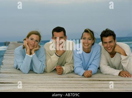 Friends lying on pier - Stock Photo