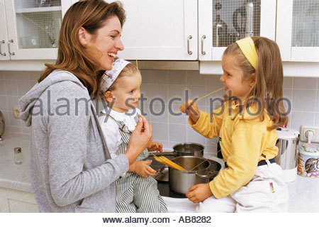 Mother and daughters in kitchen - Stock Photo
