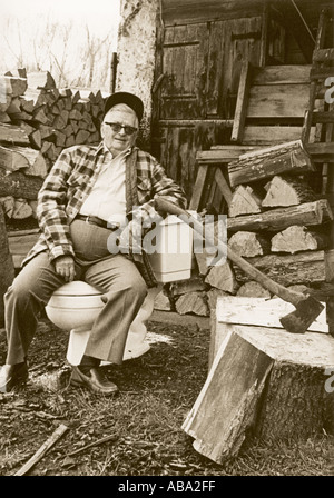 RESTING Elderly man using toilet as a resting place after chopping wood Still in church clothes Hankie in hand Photographed - Stock Photo