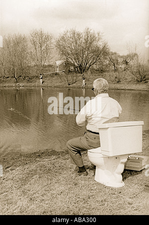 FISHING Elderly man fishing and using a toilet as his seat Still dressed in church clothes Photographed in Pennsylvania - Stock Photo