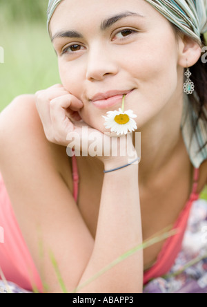 Young woman with flower in mouth, portrait - Stock Photo