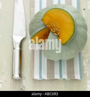 Squash with shiny knife on striped towel - Stock Photo