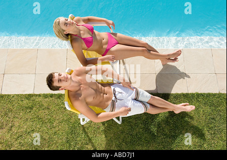 Couple sunbathing by the pool - Stock Photo