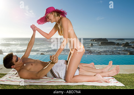Couple playfighting by pool - Stock Photo