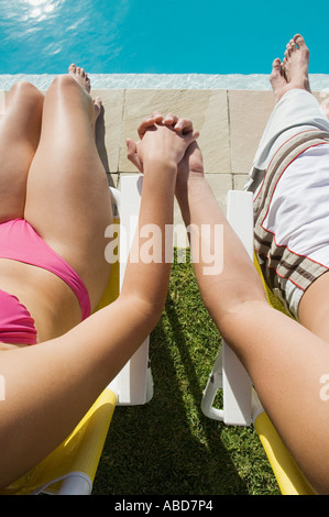 Couple holding hands by the pool - Stock Photo