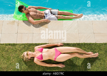 Couple sunbathing at the pool - Stock Photo