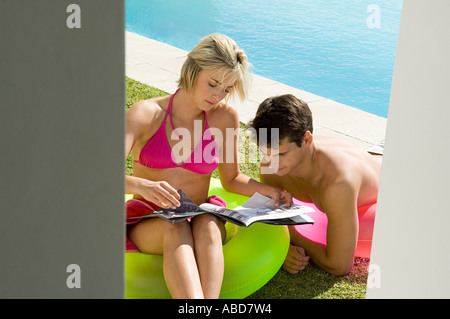 Couple reading a magazine by the pool - Stock Photo