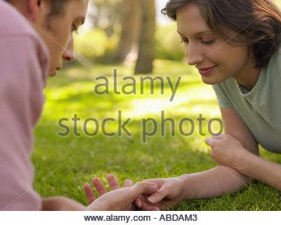 Couple lying on the grass - Stockfoto
