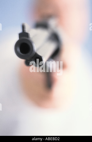 Close up of the end of a handgun being pointed as if to threaten or shoot - Stock Photo