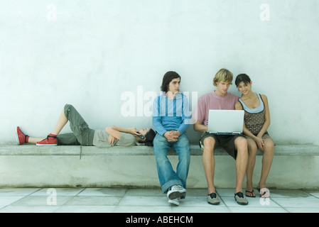 Group of young friends using laptop together - Stock Photo
