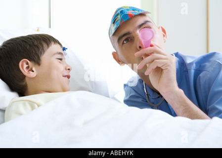 Intern next to boy in hospital bed, wearing mask and blowing party horn - Stock Photo