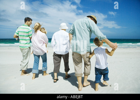Three generation family walking on beach, rear view - Stock Photo