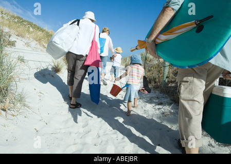 Family walking through dunes, rear view - Stock Photo