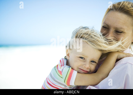 Woman holding daughter on beach, girl smiling at camera as wind tousles her hair - Stock Photo