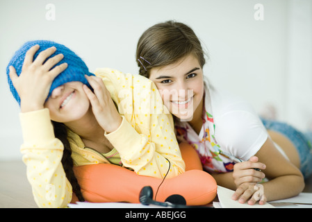 Two young female friends lying on floor, one covering eyes with knit hat - Stock Photo