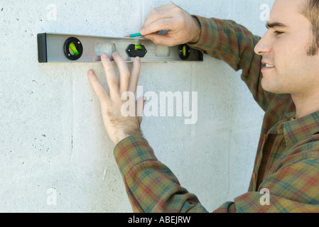Man using level to draw line on wall - Stock Photo