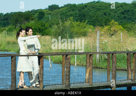 Couple standing on footbridge, woman pointing to the distance - Stock Photo