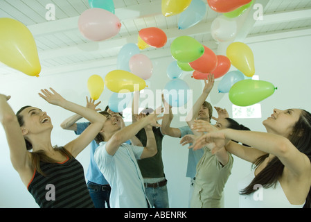 Group of young friends hitting balloons floating in the air - Stock Photo