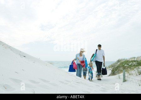 Family walking through dunes to beach - Stock Photo