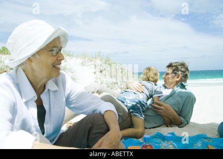 Family relaxing on beach - Stock Photo