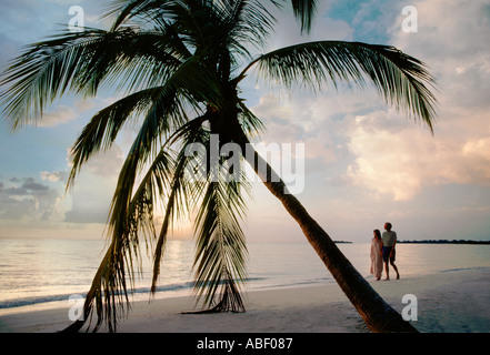 Couple walking on Long Beach Negril Jamaica WI at sunset - Stock Photo