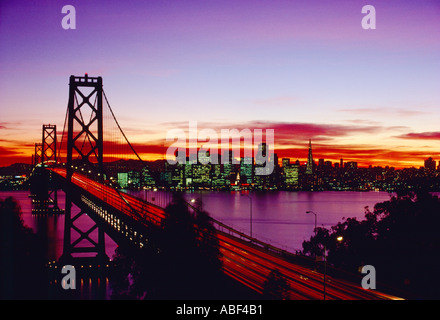San Francisco view of the skyline at sunset with the San Francisco Oakland Bay Bridge in the foreground - Stock Photo