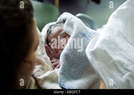 Newborn baby girl is just born at hospital. She is just 10 minutes old, wrapped in towel she is in her mum's arm. - Stock Photo