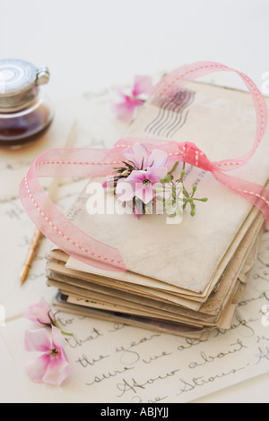 Stack of old letters next to flowers and ink bottle - Stock Photo