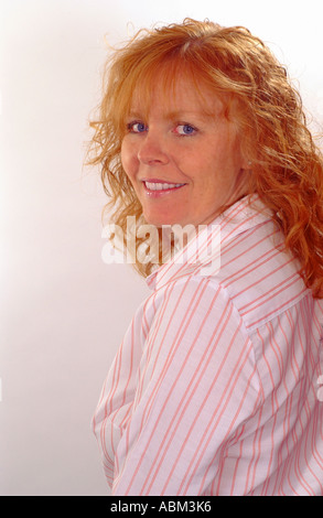 curly red headed woman looking over shoulder - Stock Photo