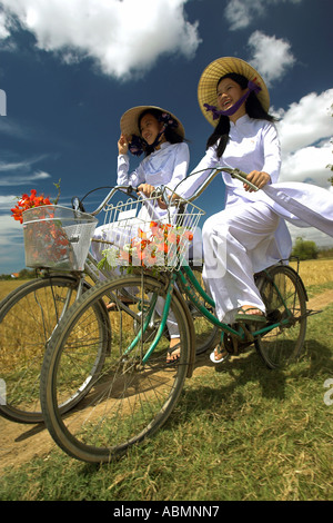 Two young women in conical hats and traditional costume ride bicycles through rice fields near Phan Thiet Vietnam - Stock Photo