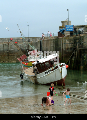 Children Playing on Beach with Fishing Boats in Newquay Harbour in Background - Stock Photo