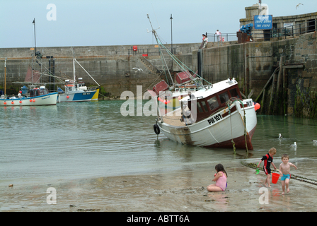 Children Playing on Beach with Fishing Boats in Newquay Harbour in Background Cornwall England United Kingdom UK - Stock Photo