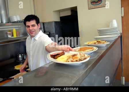 short order cook prepares food in a small restaurant stock