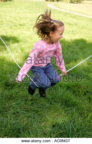 A young girl jumping over a skipping rope - Stockfoto