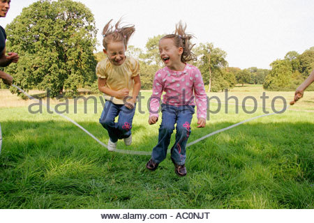 Two sisters jumping over a skipping rope - Stockfoto