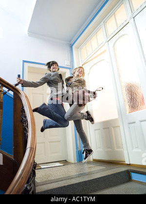 Two girls jumping on staircase - Stock Photo