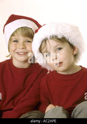 Portrait of  happy young boys in Santa hats - Stock Photo