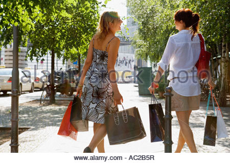 Two women walking on the street carrying shopping bags - Stock Photo