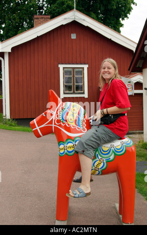 a young woman sitting on a Dala horse near Farnas in the South of Sweden - Stockfoto