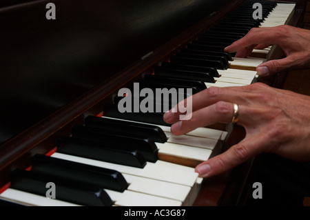Close up of mans hands playing piano - Stock Photo