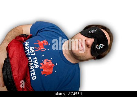 A badly shaved young man sleeping with a mask. Jeune homme dormant avec un masque occultant la lumière. - Stock Photo