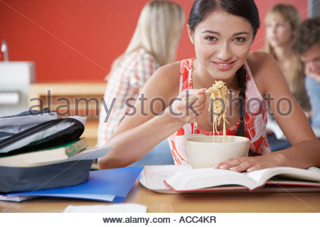 Teenage girl eating bowl of noodles with chopsticks in cafeteria - Stock Photo
