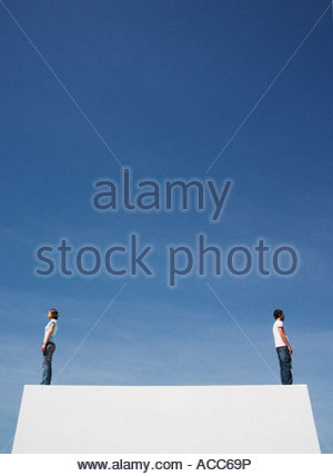 Man and woman standing on box back to back outdoors with blue sky - Stock Photo