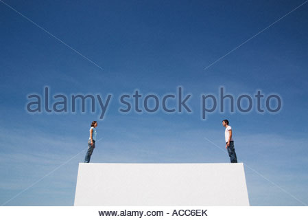 Man and woman standing on box at both ends outdoors with blue sky - Stock Photo